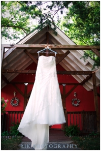 Wedding dress hanging in front of a red barn